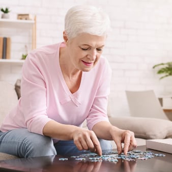 elderly woman building a puzzle