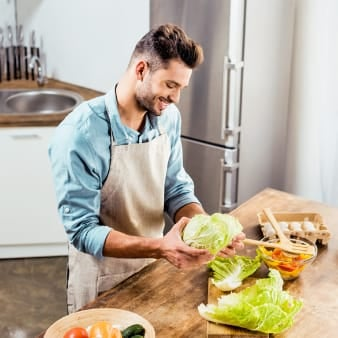 Man preparing salad in kitchen