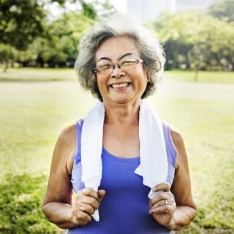 Older woman exercising in the park holding towel around neck