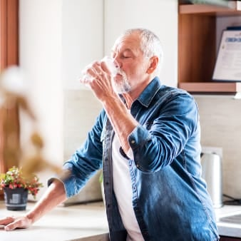 Older bearded man drinking glass of water